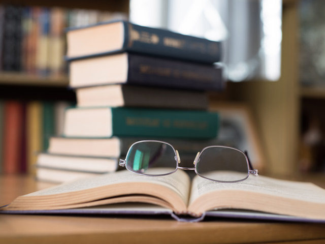 Glasses sitting on top of a book in a library